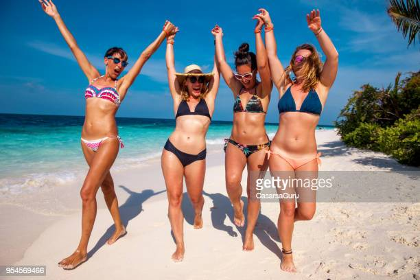 adult women enjoying together on beach - swimwear stock pictures, royalty-free photos & images