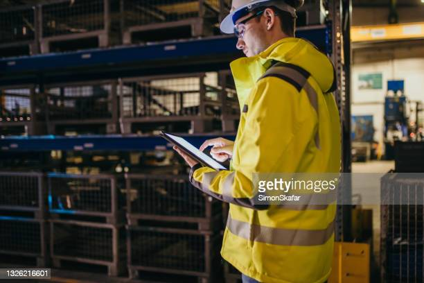 adult worker looking at digital tablet - mid adult men stock pictures, royalty-free photos & images