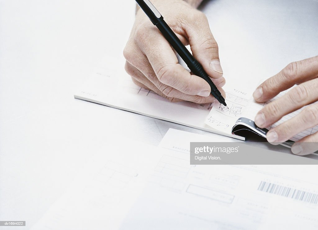 Adult Writing in a Cheque Book : Stock Photo