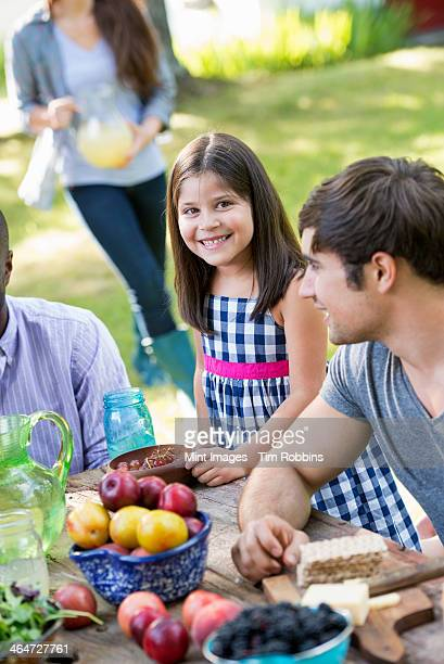 Adults and children around a table at a party in a garden.