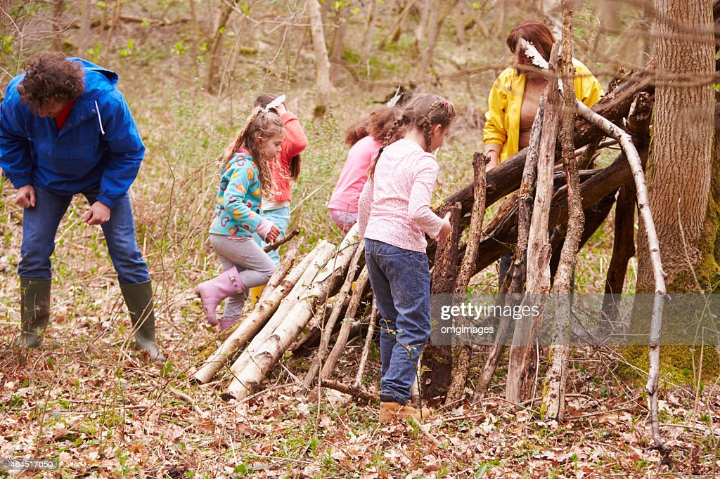 Adults And Children Building Camp At Outdoor Activity Centre : Stock Photo