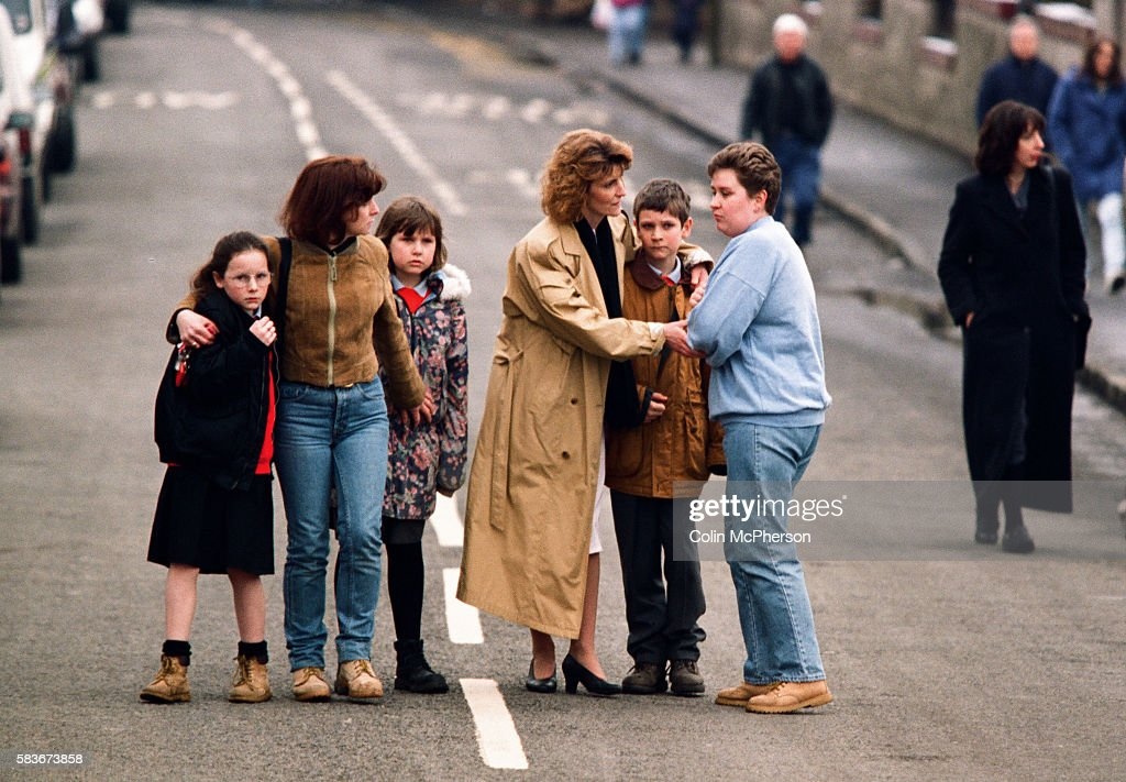 Adults And Children Comfort Each Other Outside Dunblane Primary School Scotland Shortly After The