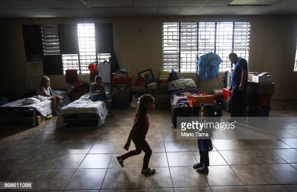Adults and children gather on Christmas day in the shelter for Hurricane Maria victims where they currently reside on December 25 2017 in Toa Baja...