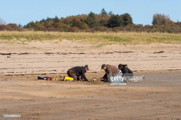 Adults and children on a quiet Scottish beach