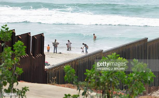 Adults and children play at the beach on the Tijuanaside of the Border Field State Park fence which separates the cities of San Diego and Tijuana...