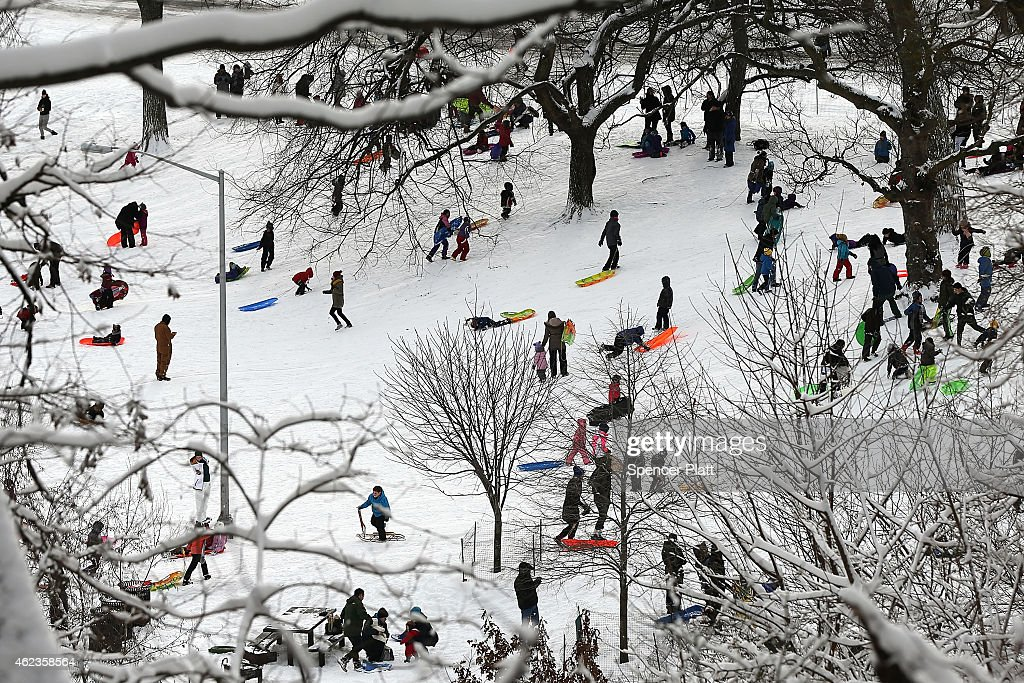 Adults and children sled at Brooklyn's Prospect Park the morning after a major winter storm on January 27, 2015 in New York City. Despite dire predictions, New York City was spared the worst of the storm, receiving up to a foot of snow in some areas. Subway buses were closed overnight while roadways were open only to emergency vehicles.
