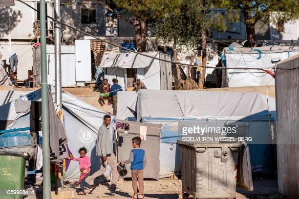 Adults and children walk inside the Moria refugee camp on Lesbos Island on November 8 2018 Greek government data released on September 17 2018 showed...
