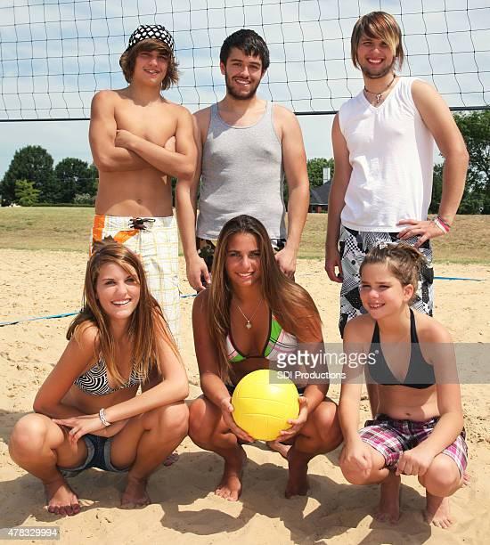 Erwachsene und Teenager spielen Sie volleyball im sand zusammen