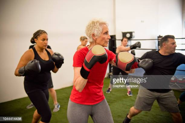 adults build strength through boxing program - mixed boxing stock photos and pictures
