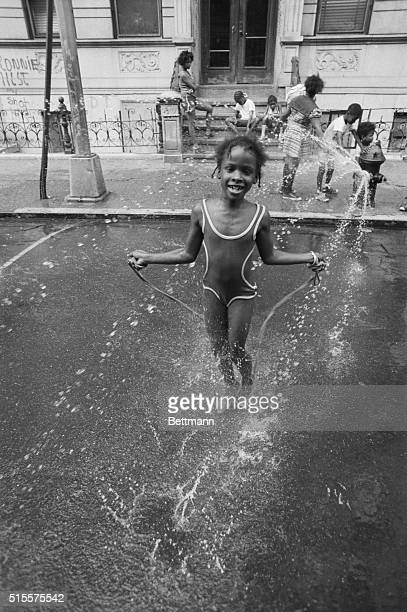 Adults can complain about the heat of summer but kids delight in it A little girl in Harlem skips away the hours in the refreshing spray of a fire...