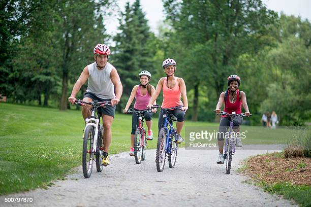 Adults Cycling Through the Park