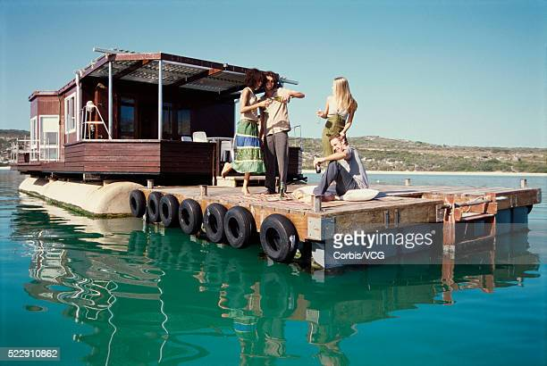 adults hanging out on a boat against blue sky - houseboat stock pictures, royalty-free photos & images