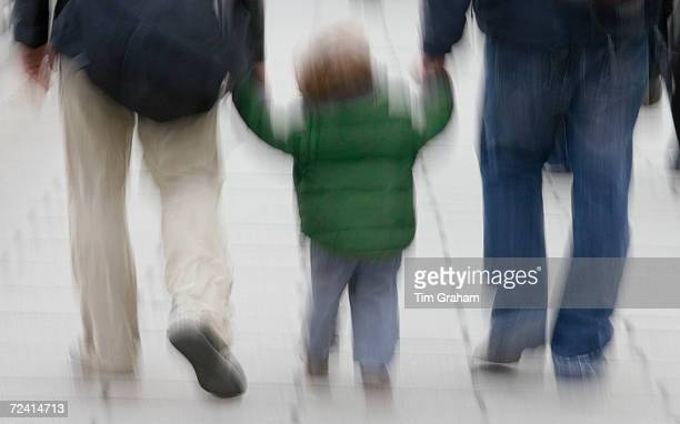 Adults hold a child's hand as they walk through London England United Kingdom