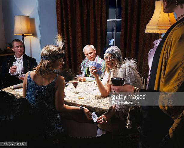 adults in fancy dress, playing cards at table, man by window outdoors - roaring 20s party stock photos and pictures
