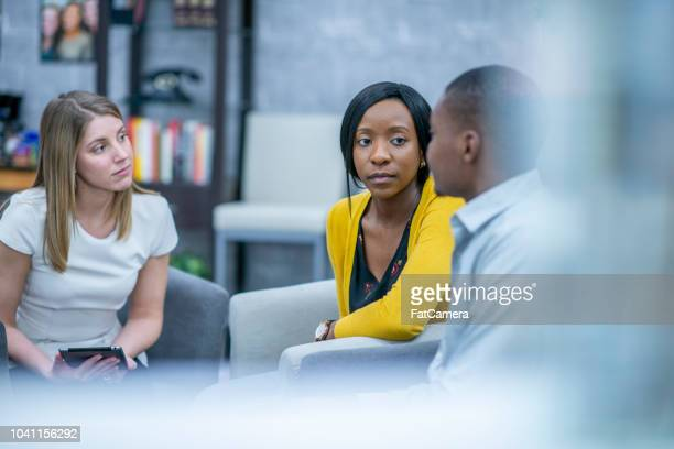 adults listen attentively to each other in a group therapy session - alcoholics anonymous stock pictures, royalty-free photos & images