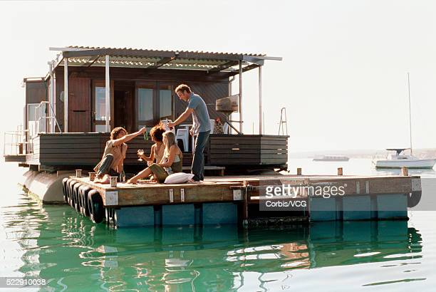 adults passing out drinks on a boat - houseboat stock pictures, royalty-free photos & images