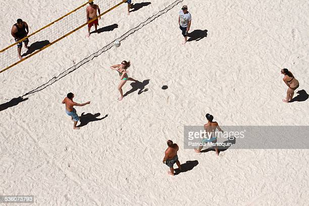Adults play volleyball in a manmade sand volleyball court in Las Vegas Nevada