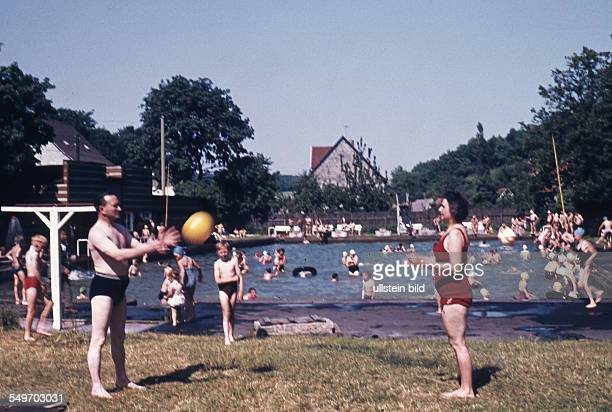 Adults play with a ball on the lawn of an open air pool 1950s