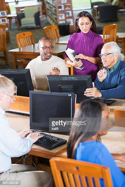 Adults studying in the library using computer