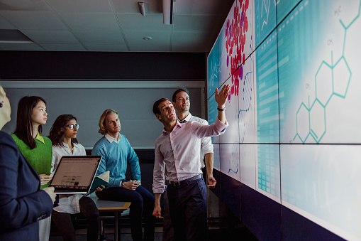 Adults Viewing Data on a Large Display Screen 872019506
