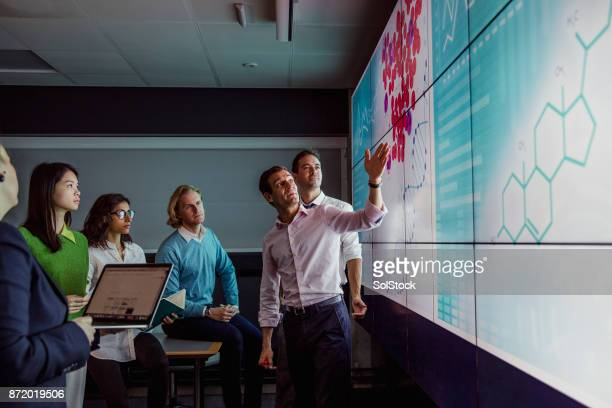 adults viewing data on a large display screen - place of research stock pictures, royalty-free photos & images