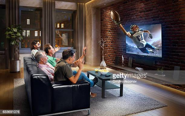 Adults watching American football game at home