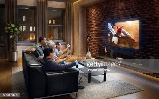 Young Men Cheering And Watching Baseball Game On Tv Stock Photo