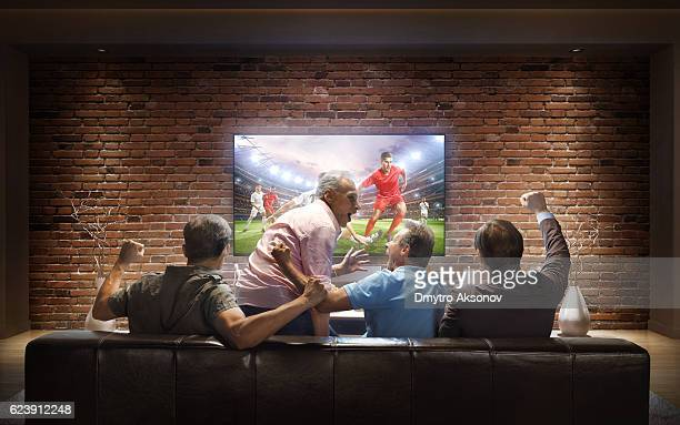 adults watching soccer game at home - match sportivo foto e immagini stock