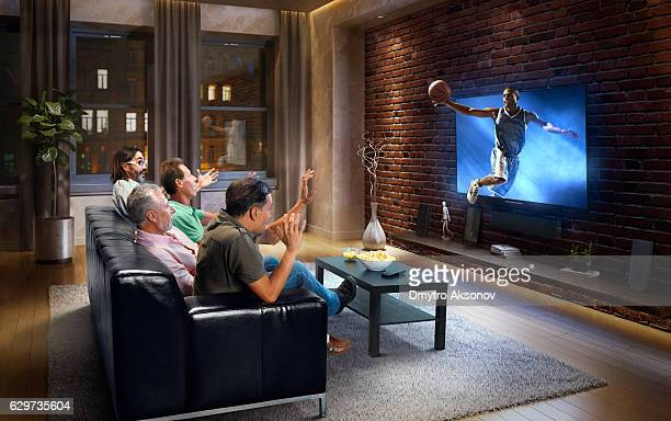 Adults watching very realistic Basketball game at home