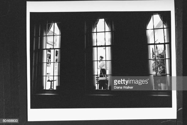 NSC Adv Brent Scowcroft in shirtsleeves talking on phone while standing in his WH office at night as seen from outside looking in through large window
