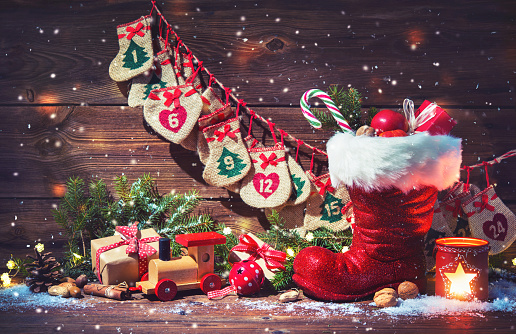 Advent calendar and Santa's shoe with gifts on rustic wooden background 869077414
