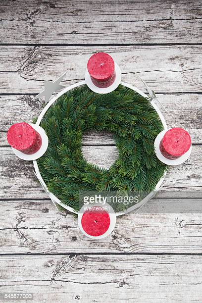 Advent wreath and four candles on wood
