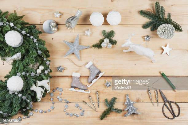 advent wreath decoration items, self-made advent wreath with real fir tree green, diy, glitter deer, snow ball candles, skates, birds, christmas baubles, vintage icicles, wire, stars, scissors, fir cone - adviento fotografías e imágenes de stock