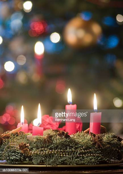 Advent wreath with four burning candles in front of Christmas tree
