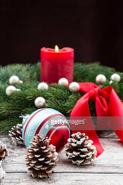 Advent wreath with lighted red candle, Christmas bauble and fir cones on wood
