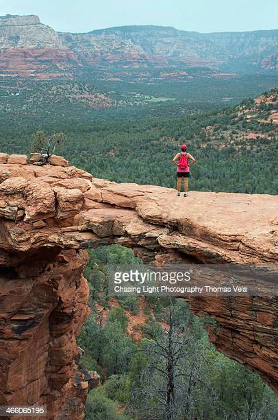 Adventerous Hiker on Natural Red Rock Bridge