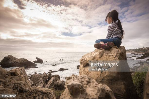 Adventerous little girl sitting on rock looking at ocean view