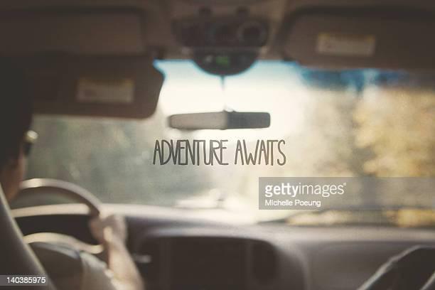 Adventure Awaits text on glass