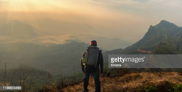Adventure backpacker traveling along green mountain on sunrise, enjoying view of mountain explore travel discover beautiful earth. Vacation concept.