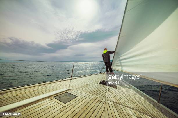 adventure man on the sailing boat - yachting stock pictures, royalty-free photos & images