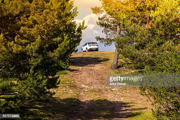 Adventure travel around the Pyrenees mountains driving with suv car to the top of the mountains with nice views on sunset.