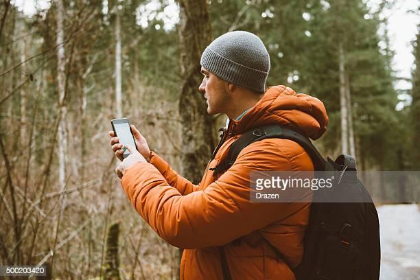 Aventurero buscando GPS señal en el bosque y excursionismo