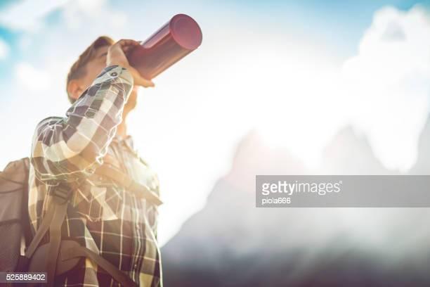 Abenteuer auf die Berge: Junge Rucksacktourist Getränke