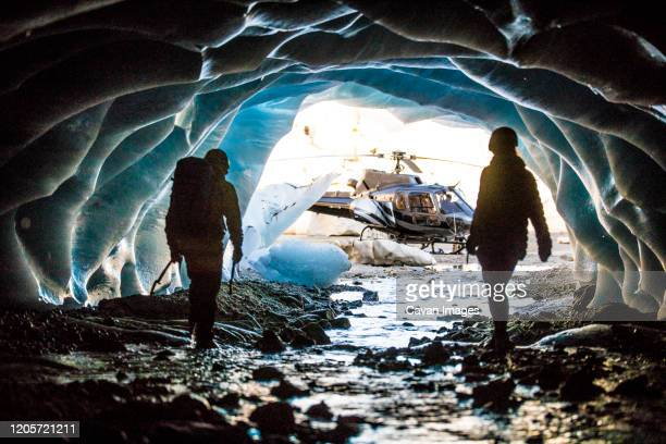 adventurous couple emerge from an ice cave to find their helicopter. - escaping stock pictures, royalty-free photos & images