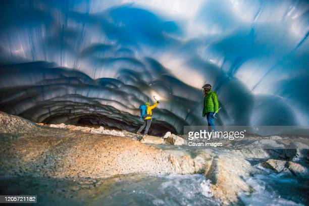 adventurous couple exploring an ice cave. - geology stock pictures, royalty-free photos & images