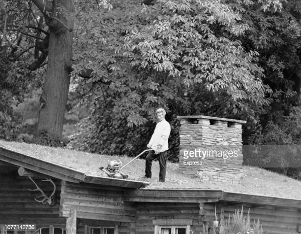 Adventurous gardener Len Lovejoy mows the lawn which is growing on the roof of his house UK 14th October 1970