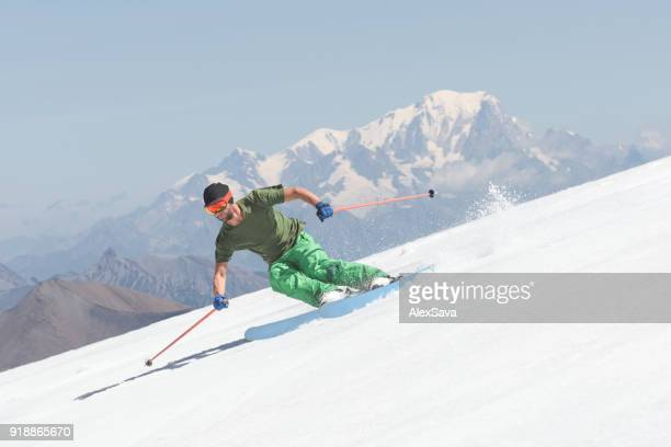 Adventurous male skier freeriding downhill snow-capped slope