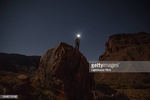 Adventurous man stands atop a large boulder at night and gazes out at landscape and stars while wearing a lit headlamp in Moab, Utah.