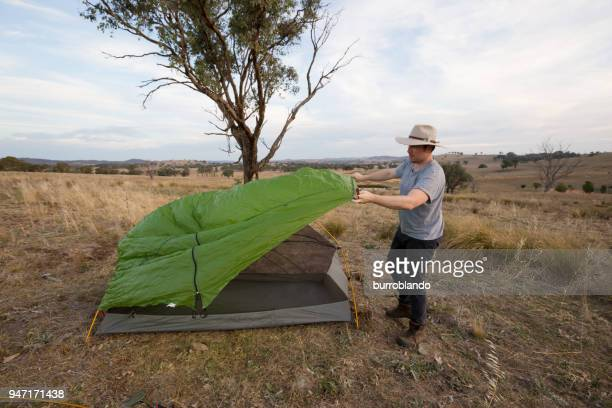 Adventurous young man adjusts the waterproof cover of his tent