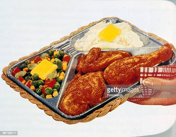 Advertisement for tv dinner with woman's hand holding complete chicken dinner in a metal holder on a wicker tray circa 1986 From 'Populuxe' by Thomas...